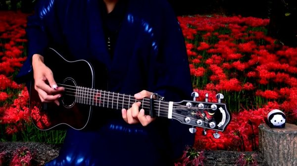 """『鬼滅の刃』OP曲『紅蓮華』をアコギで弾いてみた! """"一面の曼殊沙華""""を背景にした演奏へ「カッコイイ」「ギターに映り込んだ赤がまたよき」の声"""